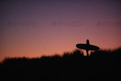 Silhouette Of Female Surfer Carrying Surfboard Across Dunes Against Setting Sun