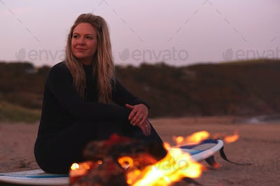 Woman Sitting On Surfboard By Camp Fire On Beach As Sun Sets Behind Her