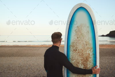 Rear View Of Young Man Wearing Wetsuit Enjoying On Surfing Staycation Looking Out To  Sea At Waves