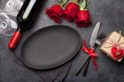 Valentines day with empty plate, gift, wine and roses