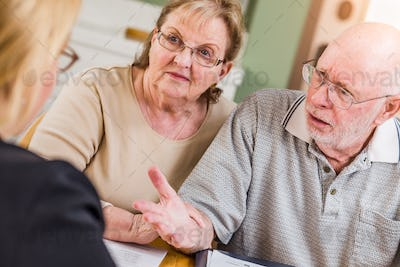 Senior Adult Couple Going Over Documents in Their Home with Agent At Signing