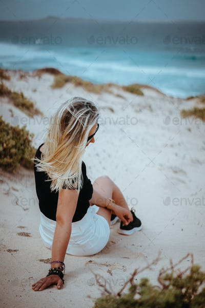 Woman sitting in white sand dune with Atlantic coastline landscape. Ocean waves hitting coast in