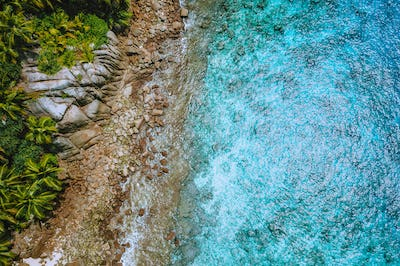 Aerial drone view of tropical coastline, crystal clear turquoise ocean water, bizarre granite rocks