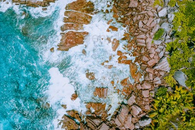 Aerial drone photo of Seychelles tropical beach Anse Cocos at La Digue Island. White rolling waves