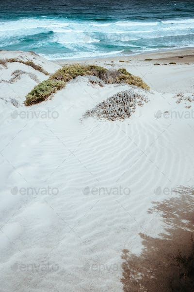 Stunning desolate landscape of sand dunes, ocean waves on Baia Das Gatas. North of Calhau, Sao