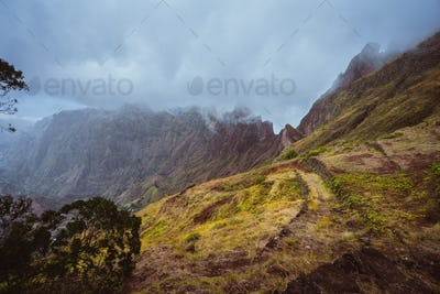 Trekking path along the mountain edge overgrown with verdant grass. Mountain peaks are covered by