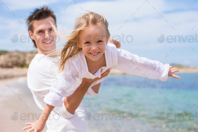 Happy father and little girl have fun during beach vacation