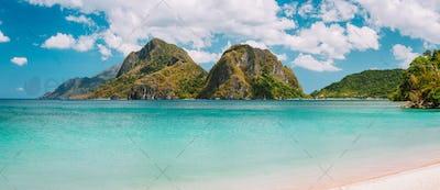 El Nido, Corong Corong beach with massive limestone mountain ridge top with blue lagoon in front