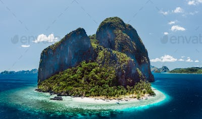 Aerial drone view of tropical Pinagbuyutan Island and ipil beach in blue ocean El Nido, Palawan