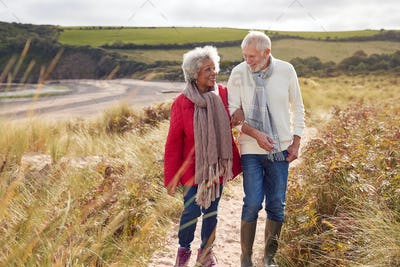 Loving Active Senior Couple Walking Arm In Arm Through Sand Dunes On Winter Beach Vacation