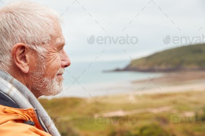 Profile Shot Of Active Senior Man Walking Along Coastal Path In Winter With Beach And Cliffs Behind