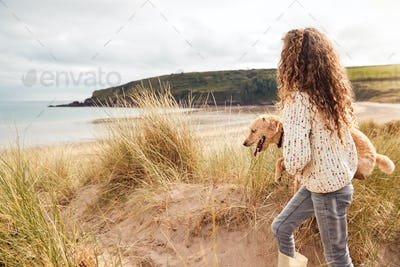 Girl Carrying Pet Dog Exploring Sand Dunes On Winter Beach Vacation