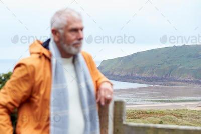 Defocused Shot Of Active Senior Man Walking Along Coastal Path In Fall Or Winter By Gate