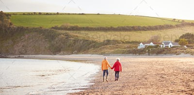 Wide Angle Rear View Of Senior Couple Holding Hands Walking Along Shoreline On Winter Beach Vacation