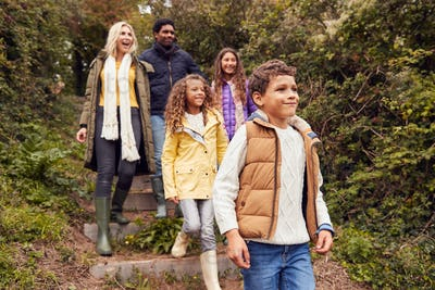 Multi-Cultural Family Walking Down Steps In Countryside On Winter Beach Vacation