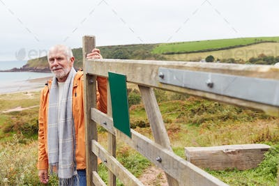 Active Senior Man Walking Along Coastal Path In Winter Opening Gate With Beach And Cliffs Behind