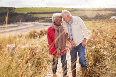 Loving Active Senior Couple Walking Arm In Arm Through Sand Dunes On Winter Beach Vacation