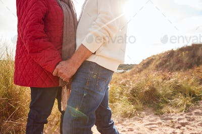 Close Up Of Loving Senior Couple Holding Hands Walking Through Sand Dunes On Winter Vacation