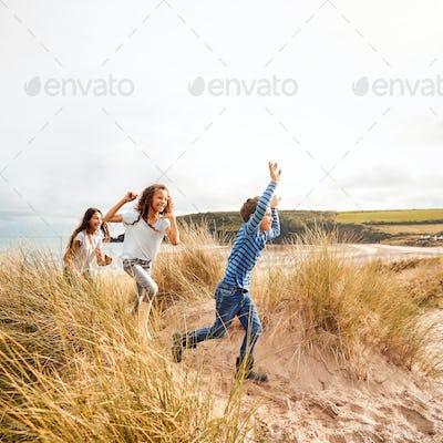 Three Children Having Fun Exploring In Sand Dunes On Winter Beach Vacation