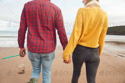 Rear View Of Loving Couple Holding Hands Walking Along Beach Shoreline On Winter Vacation