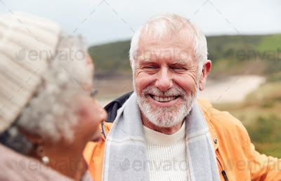 Close Up Of Loving Active Senior Couple Taking A Break As They Walk Along Coastal Path In Winter