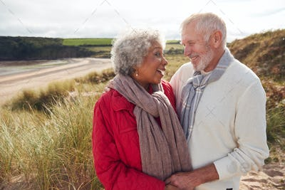 Loving Active Senior Couple Standing And Hugging On Walk In Sand Dunes On Winter Beach Vacation