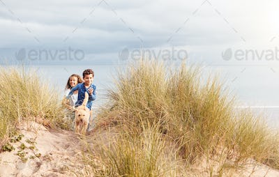 Two Children With Pet Dog Having Fun Exploring In Sand Dunes On Winter Beach Vacation