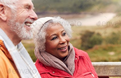 Close Up Of Loving Active Senior Couple Resting By Gate As They Walk Along Coastal Path In Winter