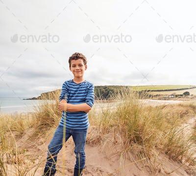 Portrait Of Boy Exploring Sand Dunes On Winter Beach Vacation