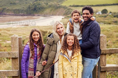 Portrait Of Active Multi-Cultural Family Standing By Gate On Winter Beach Vacation