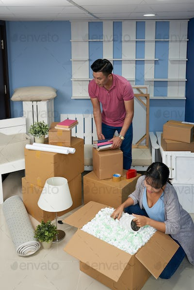 Couple Unpacking Boxes At Home