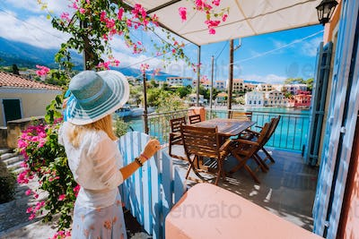 Female tourist with blue hat staying in Assos village in front of cozy veranda and admiring
