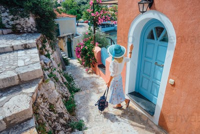 Travel tourist blonde woman with sun hat walking through narrow streets of an old greek town to the