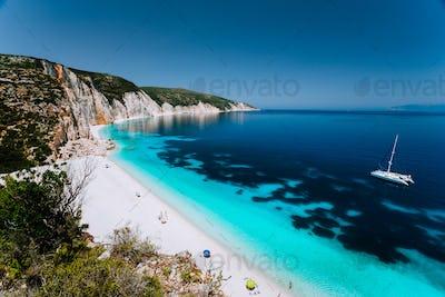 White catamaran yacht in clear blue sea water. Tourists on sandy beach near azure sea lagoon