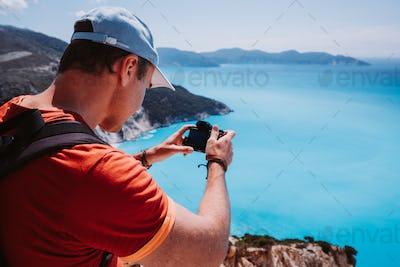 Man capture photograph of myrtos coastline sea landscape. Blue cyan water surface with island shape