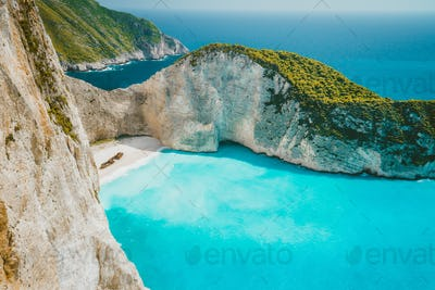 Famous shipwreck on Navagio beach with turquoise blue sea water surrounded by huge white cliffs