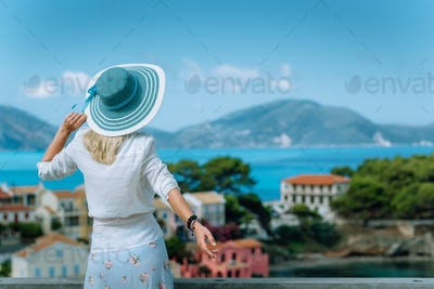 Assos in morning light. Young tourist woman wearing blue sunhat and white clothes admiring view of