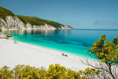 Amazing Fteri beach lagoon, Cephalonia Kefalonia, Greece. Tourists under umbrella relax near clear