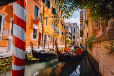 Gondolas boat floating in narrow canal of Venice city on beautiful sunny day. Italy. Europe