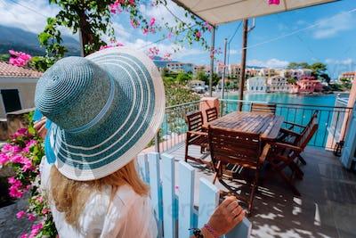 Assos village, Kefalonia, Greece. Female tourist in blue sunhat in front of cozy veranda terrace