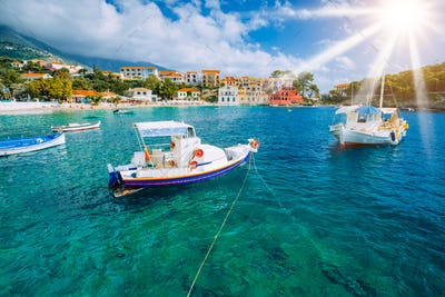 Cozy Assos village in Kefalonia. Colorful boats in azure bay under morning sunlight. Sommer vacation