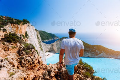 Male tourist enjoying spectacular view from the highs to Navagio beach on Zakynthos island