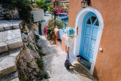 Travel tourist woman on vacation in Greece. Person with blue sunhat in front of traditional