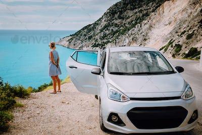 Women near rented car with open door enjoying Myrtos Beach. Travel vocation concept. Kefalonia