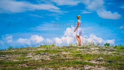 A girl standing on Hill and looking at the white clouds, Teletubbies Hills, Nusa Penida, Bali
