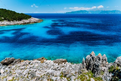 Remote lagoon with pure crystal clean turquoise sea water, surrounded by cypress trees and white