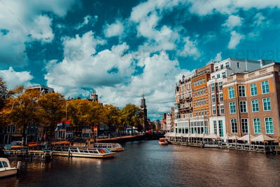 City view of Amsterdam with cruise boats and typical brick houses on sunny day with Vibrant fluffy