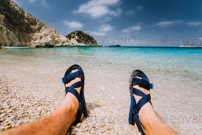 Young male feets wear blue flip-flop sandal sunbathing on sea beach with clear water