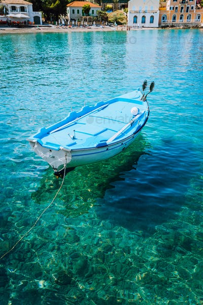 Blue fishing boat in the emerald azure rippled sea water bay in Assos village, Kefalonia island