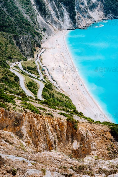Serpentine zigzag road down to famous Myrtos Beach. Many tourists on the sunny beach, Kefalonia